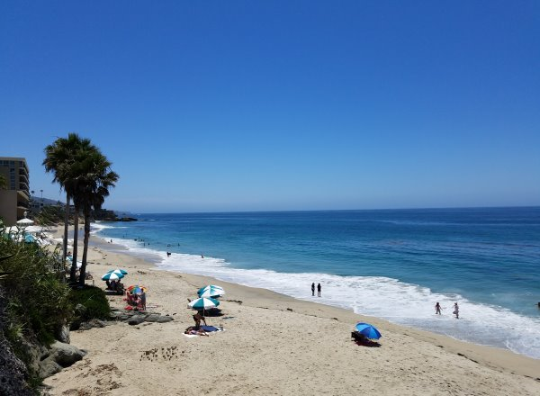 people on the sandy beach at mountain road beach in laguna beach ca