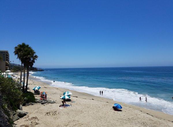 people on the sandy beach at mountain road beach in laguna beach ca